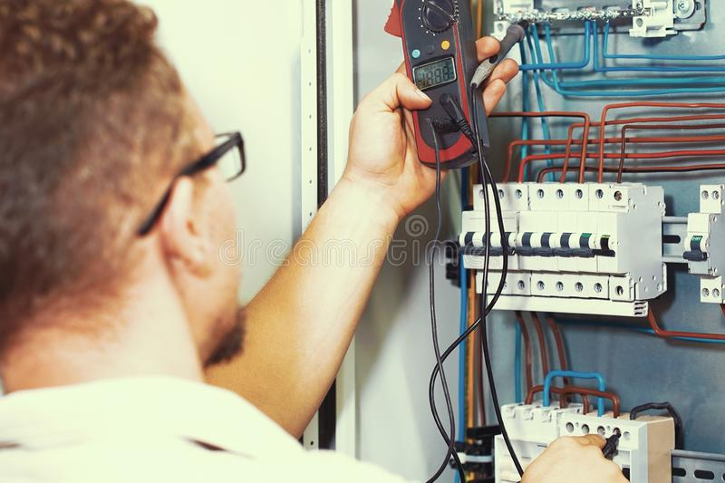 Multimeter is in hands of electrician on background of electrical automation cabinet stock image