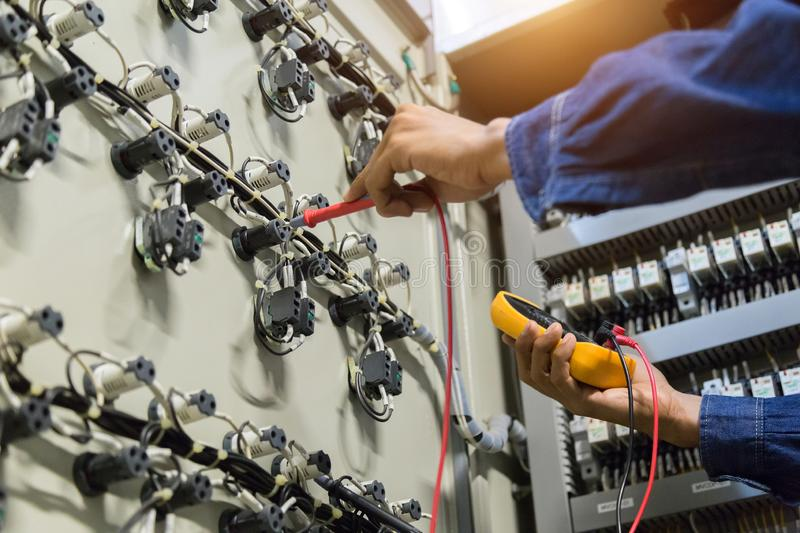 Electrician engineer work  tester measuring  voltage and current of power electric line in electical cabinet control royalty free stock photography