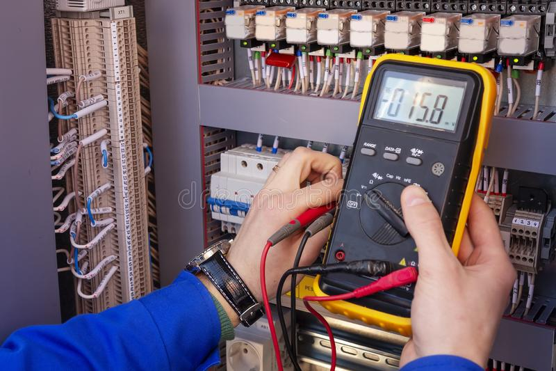 Multimeter in hands of electrician engineer in electrical cabinet. Maintenance of electric system. Worker tests of electrical circuit. Electrician with tester royalty free stock photography