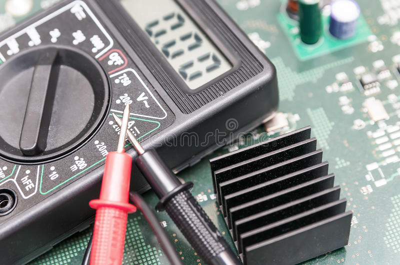 Multimeter on PCB plate. Close-up multimeter on PCB plate royalty free stock photography