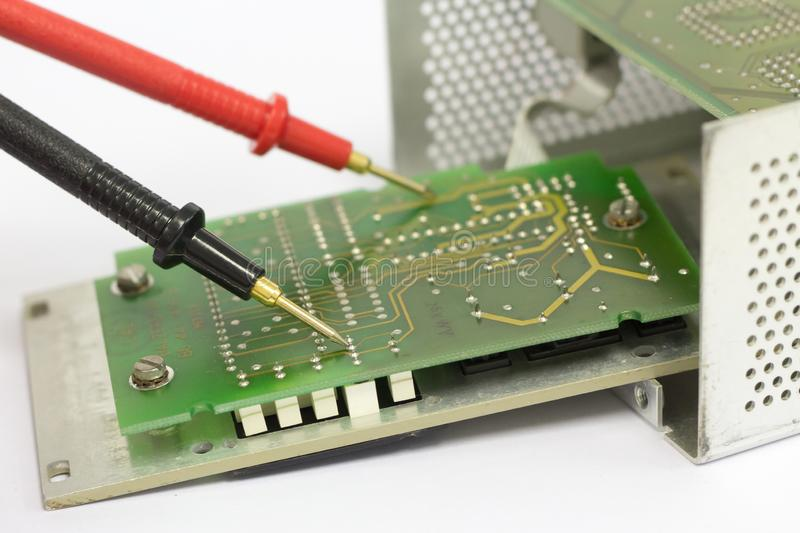 Multimeter probes on printed circuit board. stock photo