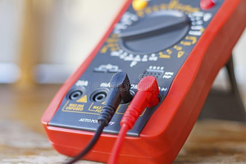 Multimetro di Digital con le sonde collegate su una tavola di legno fotografia stock