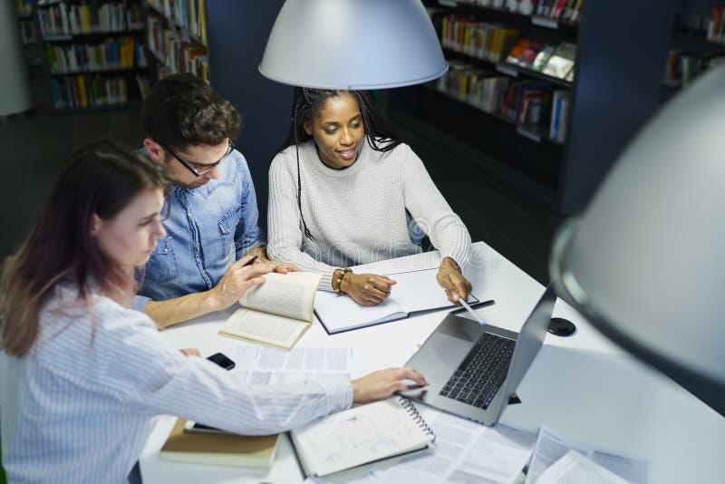 Multinationaal team van bedrijfsschoolstudenten die bij Desktop in universitaire bibliotheek zitten stock fotografie