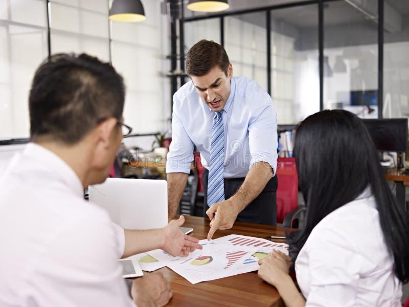 Multinationaal zakenlui die verkoopprestaties binnen weg bespreken stock afbeelding