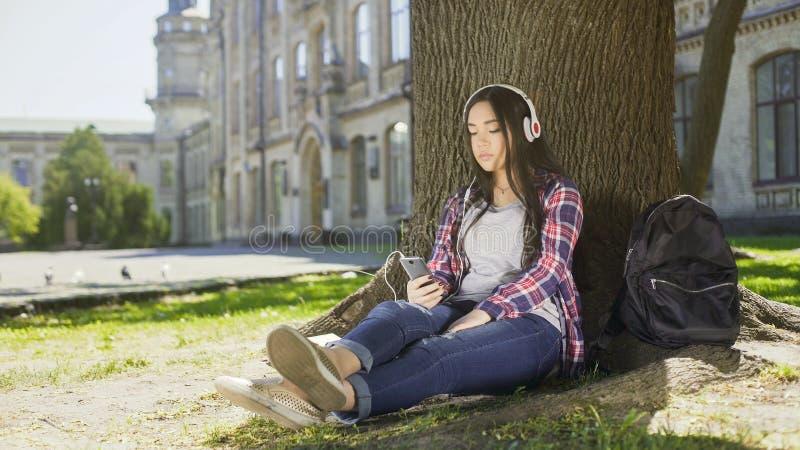 Multinational girl sitting under tree in headphones, using phone, choosing song stock photo