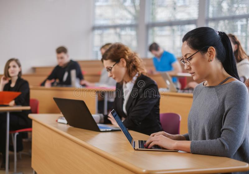 Multinational group of students in an auditorium royalty free stock photo