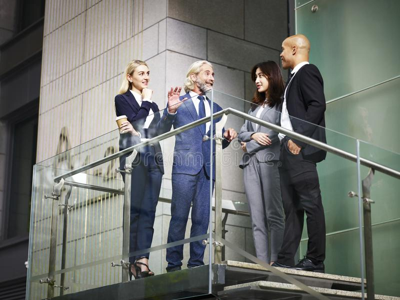 Multinational and multiethnic corporate executive talking chatting stock photo