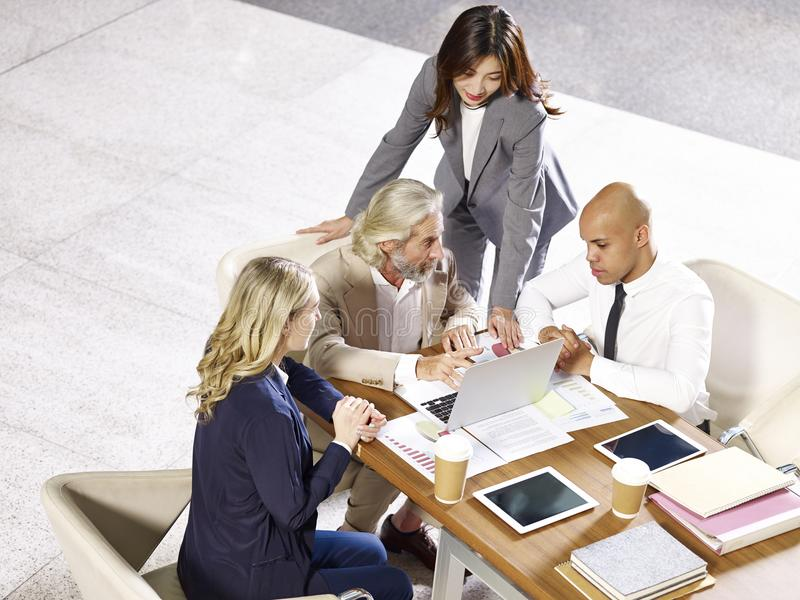 Multinational and multiethnic corporate business people meeting. Multinational and multiethnic corporate executives meeting in office discussing business stock image