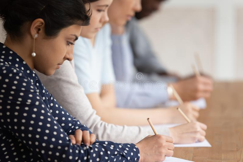 Multinational students seated at desk in row holding pencils writing on papers royalty free stock photos