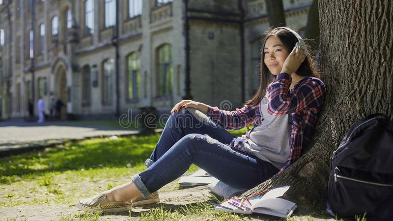 Multinational young woman in headphones sitting under tree, listening to music royalty free stock photos