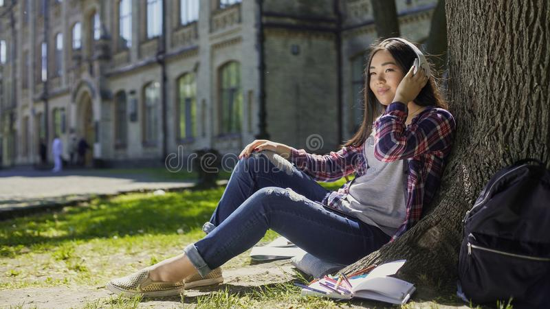 Multinational young woman in headphones sitting under tree, listening to music stock photos