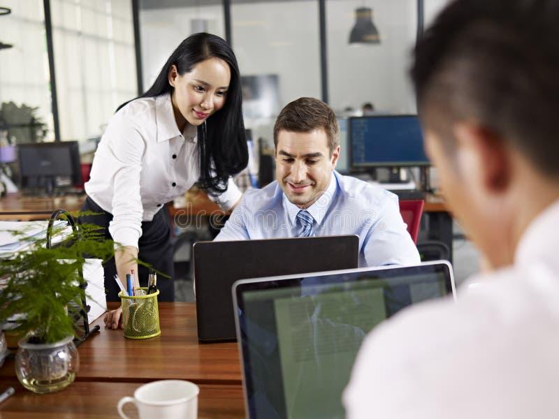 Multinationale bedrijfsmensen die in bureau samenwerken royalty-vrije stock afbeeldingen