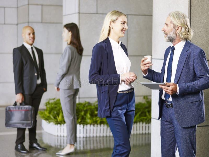 Multinationale Unternehmensleute, die in der Lobby des Modus sprechend stehen stockfotos