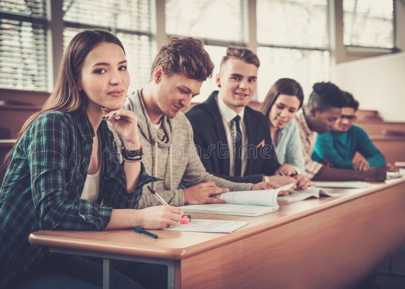 Multinationell grupp av gladlynta studenter som tar en aktiv del i en kurs, medan sitta i en hörsal arkivbild