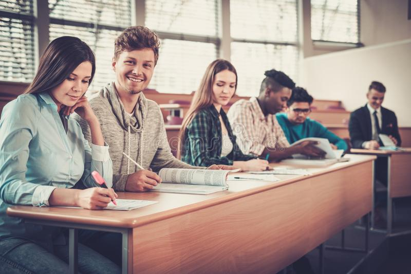 Multinationell grupp av gladlynta studenter som tar en aktiv del i en kurs, medan sitta i en hörsal royaltyfri fotografi