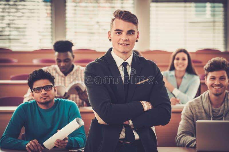Multinationell grupp av gladlynta studenter som tar en aktiv del i en kurs, medan sitta i en hörsal royaltyfria bilder
