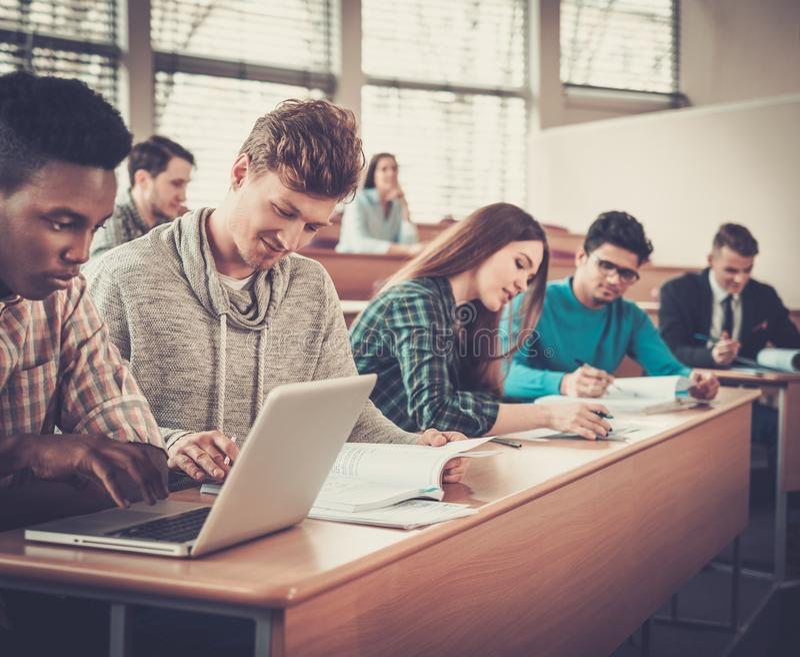 Multinationell grupp av gladlynta studenter som tar en aktiv del i en kurs, medan sitta i en hörsal arkivfoto