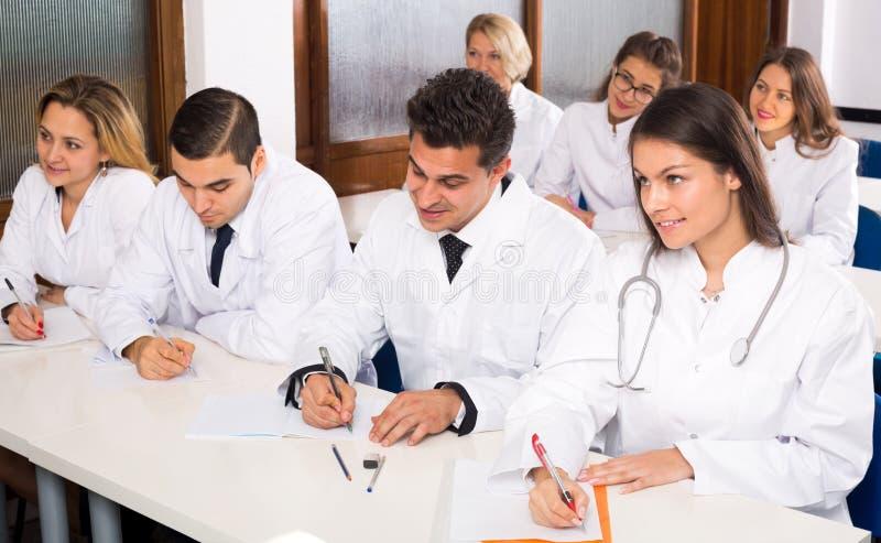 Multinationellt företagallmäntjänstgörande läkare och professor som har diskussion arkivbild