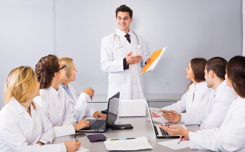 Multinationellt företagallmäntjänstgörande läkare och samarbeta för professor arkivbilder