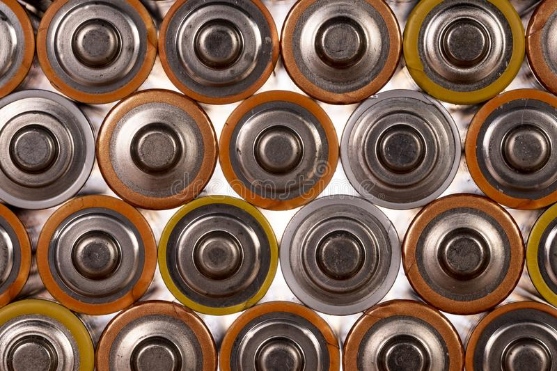 Multiple AA batteries. Multiple used AA alkaline batteries are seen arranged in a pile. Closeup front view from the plus side of the battery stock photos