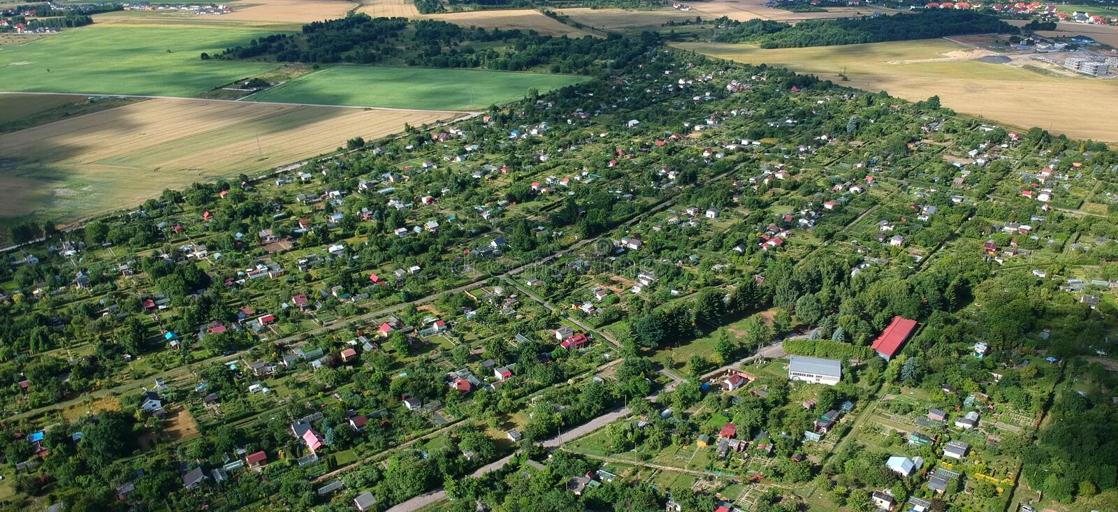 Multiple allotment gardens with little arbors, greenhouses, trees and bushes, aerial view stock photography