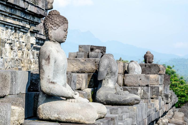 Multiple ancient stone sculptures of Buddha on the relief in Borobudur Temple in Yogyakarta, Java, Indonesia. royalty free stock photo