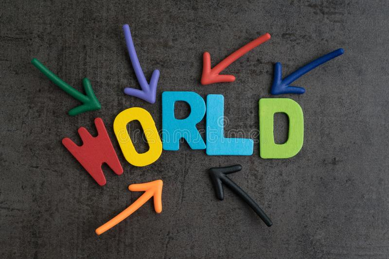 Multiple arrow pointing to wooden alphabets building the word WORLD at the center of cement chalkboard wall, important of world royalty free stock image