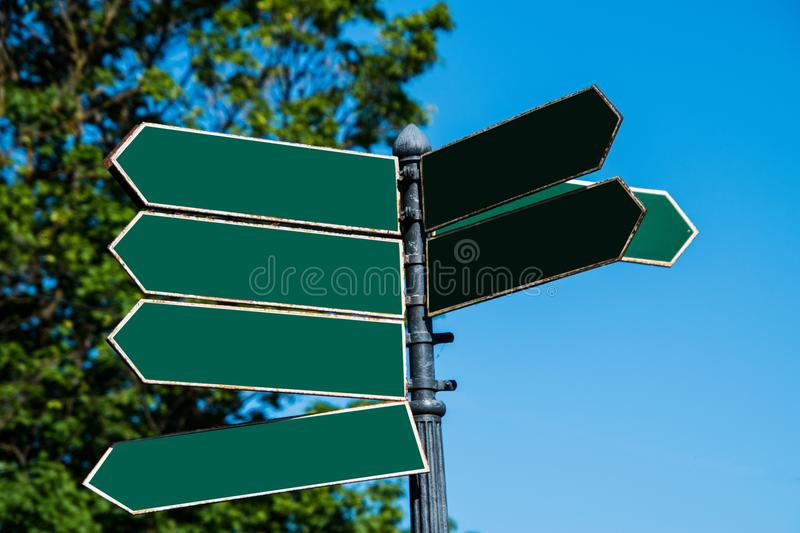 Multiple blank green arrow shaped directional street signs pointing in various directions. Multiple blank green arrow shaped directional street signs on a pole stock images