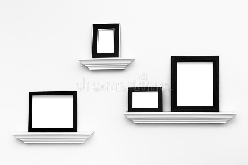 Multiple Blank picture frames on Ledges on a wall. Multiple black and white picture frames on picture ledges attached to a white wall - ready for your custom royalty free stock images