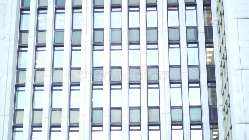 Multiple closed windows on a large, white blur office building, geometric background with lots of window rows. Many stock photos