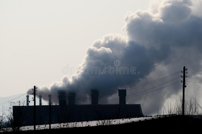 Multiple coal fossil fuel power plant smokestacks emit carbon dioxide pollution. Pollution. Multiple coal fossil fuel power plant smokestacks emit carbon royalty free stock photos