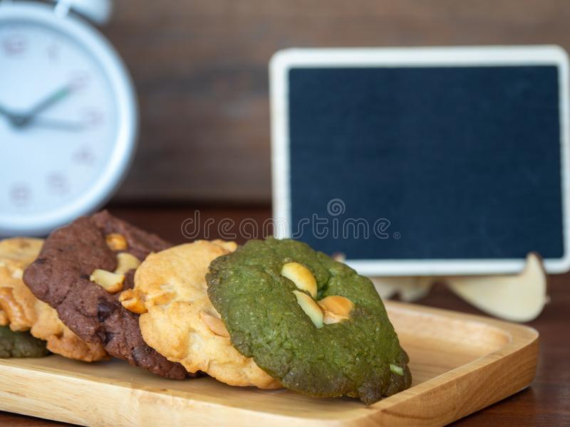 Multiple color cookies inclusive peanut butter, green tea cookies, and Chocolate Chip Cookies. Overlaid by alternating colors on w. Ood plate. White clock and royalty free stock photo