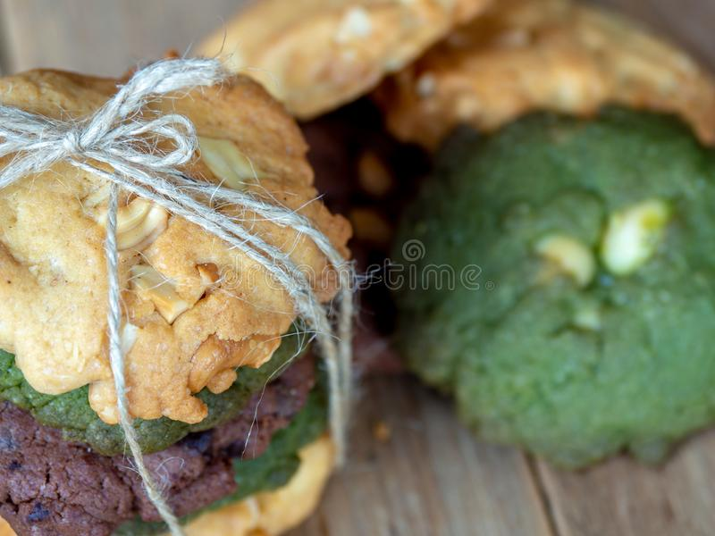 Multiple color cookies inclusive peanut butter, green tea cookies, and Chocolate Chip Cookies. Overlaid by alternating colors on w. Ood table royalty free stock images