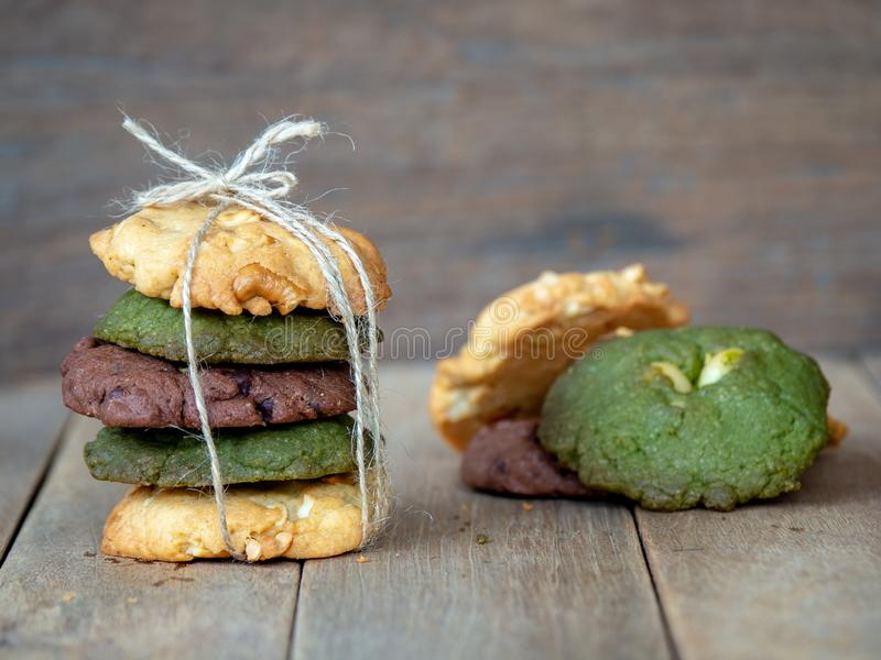 Multiple color cookies inclusive peanut butter, green tea cookies, and Chocolate Chip Cookies. Overlaid by alternating colors on w. Ood table stock photography
