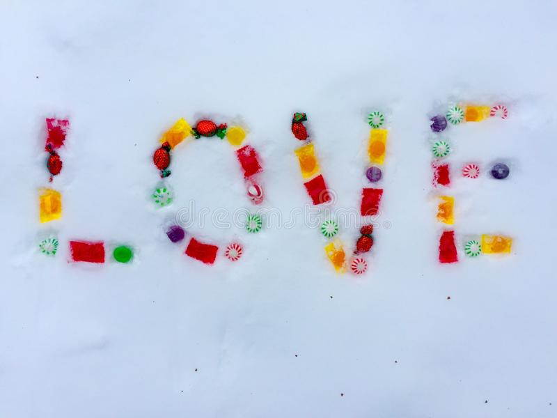 Multiple colored candies in snow spelling love stock images