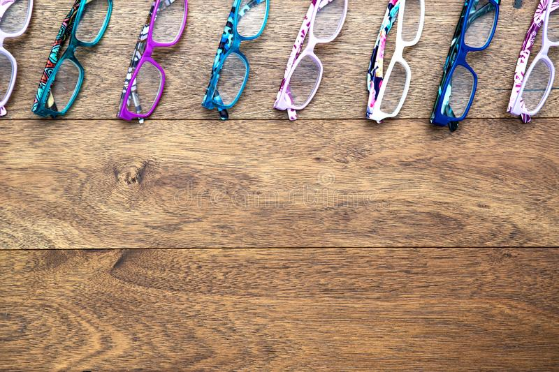 Multiple colored eye glasses lined on wooden deck.  Eye Health Concept. Top View with room for text. Specs stock image