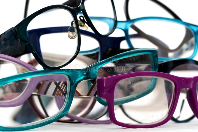 Multiple colored eye glasses in a pile on white background. Eye Health Concept stock image