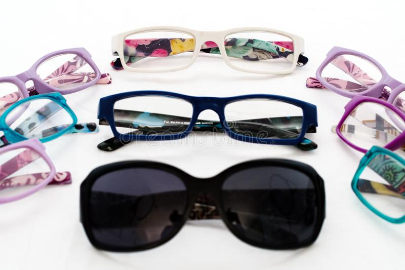Multiple colored eye glasses and sunglasses on white background. Eye Health Concept royalty free stock photography