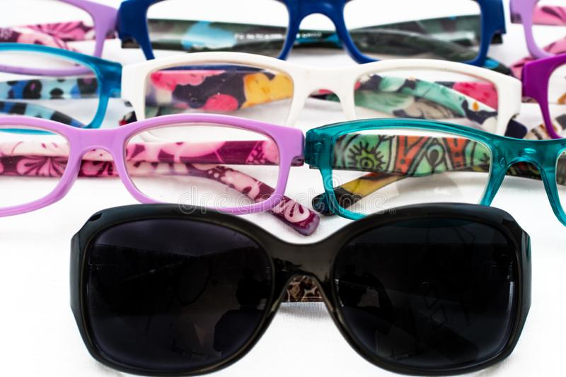 Multiple colored eye glasses and sunglasses on white background. Eye Health Concept royalty free stock image