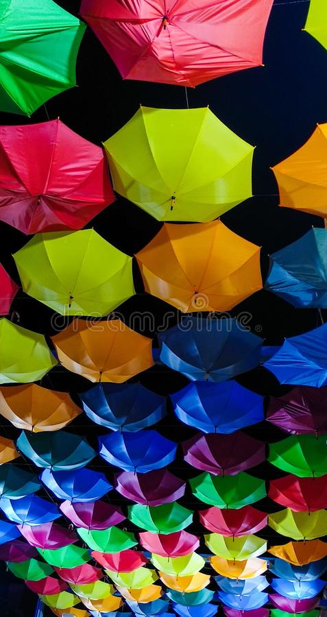 Multiple colored opened umbrellas hanging from the ceiling ordered by color rows, like a rainbow, in Oropesa (Spain stock photography