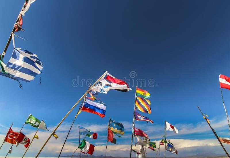 Multiple country flags against the wind at Plaza de las Banderas Uyuni. In Salar de Uyuni stock photo