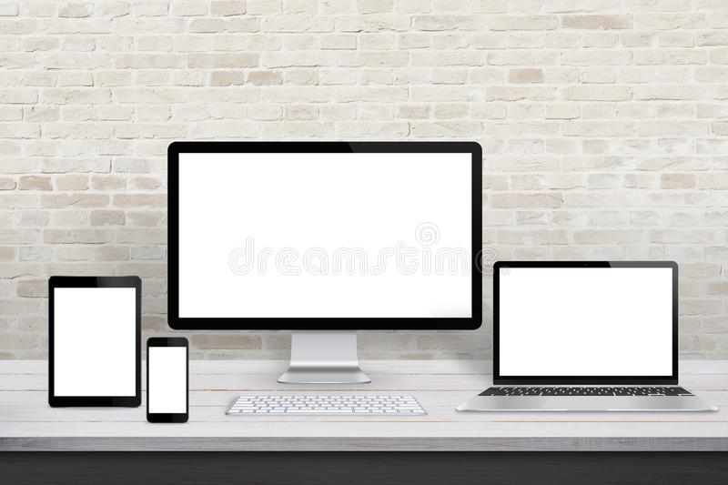 Multiple display devices for responsive web desing promotion. Modern office desk with brick wall in background royalty free stock photography