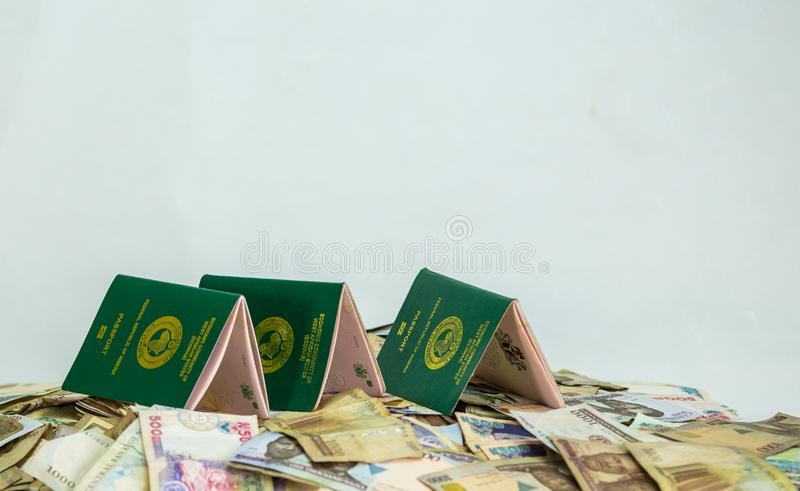 Multiple Ecowas Nigeria International Passport on a heap of local naira currencies. International Passport with local currency notes stock photography