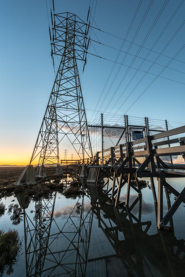Electrical towers with leading lines at sunset, with reflections in water. Multiple electrical towers with criss crossing cables leading off to the horizon. At stock photography
