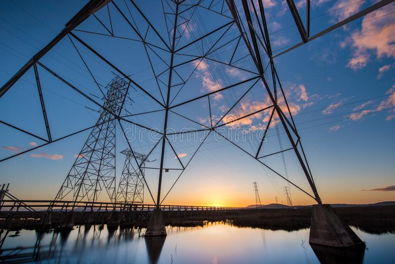 Electrical towers with leading lines at sunset, with reflections in water. Multiple electrical towers with criss crossing cables leading off to the horizon. At stock image