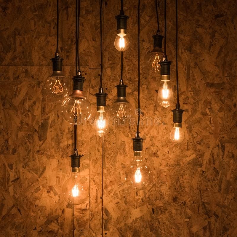 Multiple light bulbs hanging from ceiling, wooden background stock photography