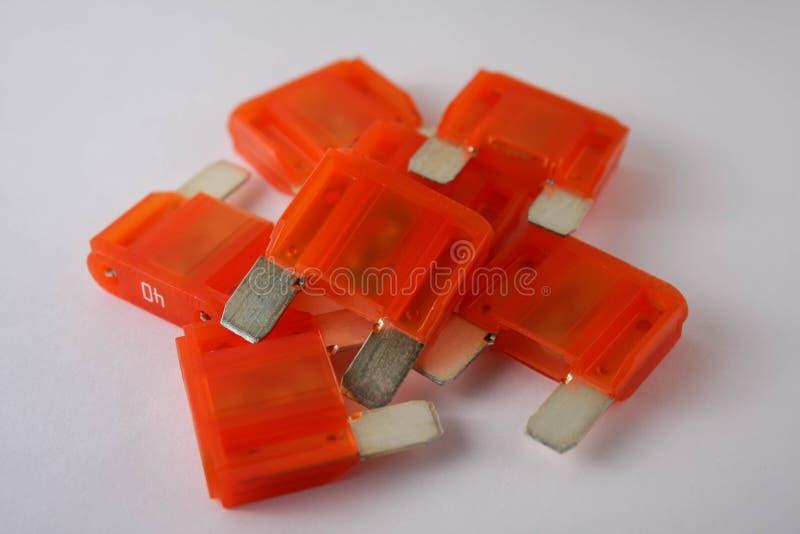 Orange car fuses on white background. Multiple orange car fuses on white background, close range view stock photos