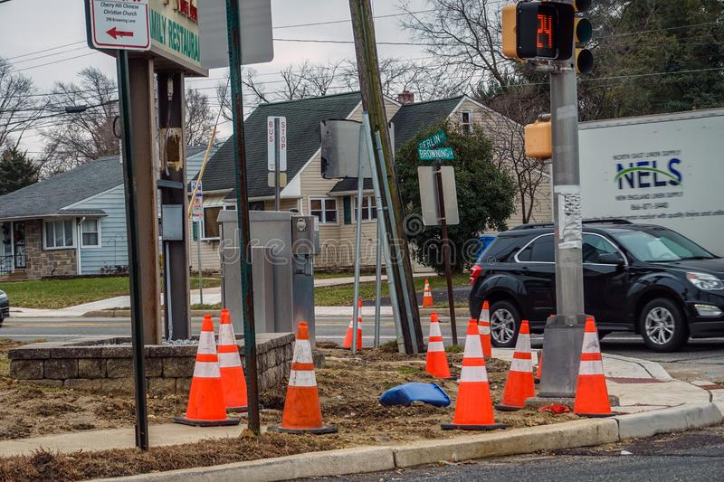 Multiple orange warning cones at a busy corner where sidewalk construction is being done stock image