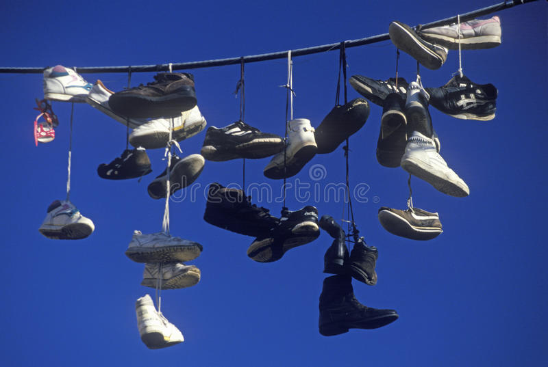 Multiple pairs of shoes flung over electric wire by shoelaces royalty free stock image