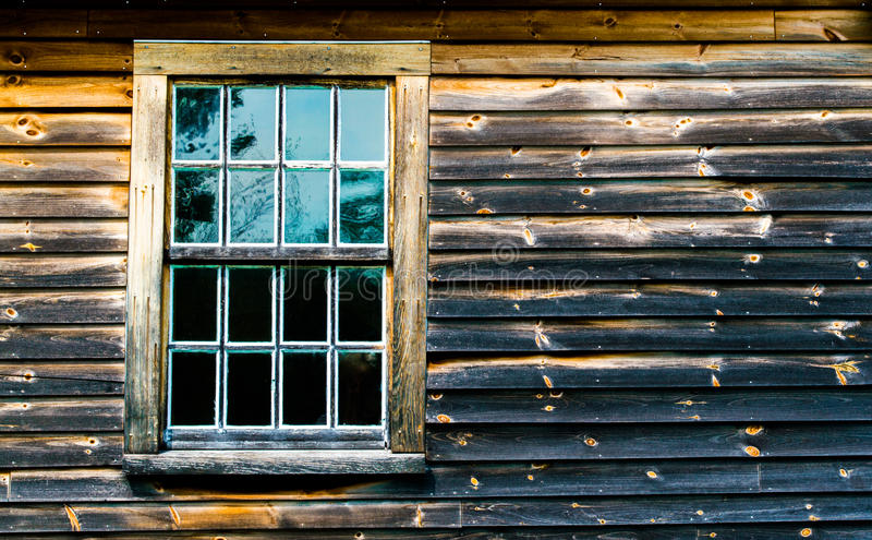 1 multiple paned window in a weathered and charred wooden wall. Of a colonial barn stock photos